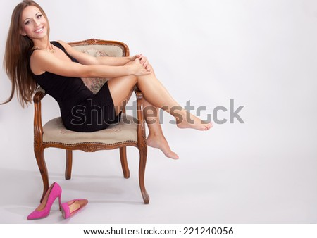 Fashionable beautiful brunette woman sitting, smiling, looking at camera - stock photo