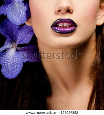 Fashionable beautiful woman with orchid in her hair - stock photo