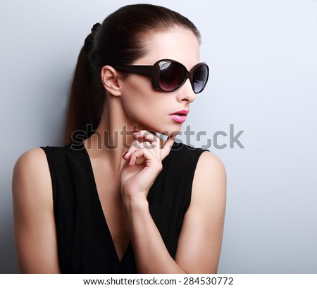 Fashionable beautiful young female model profile in sun glasses posing on blue background - stock photo