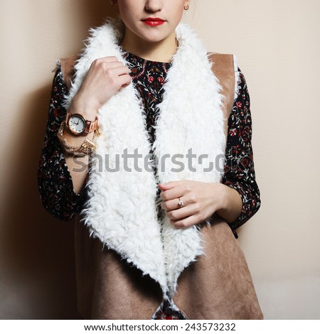Fashionable beautiful young girl in warm cardigan and vest with accessories light background - stock photo