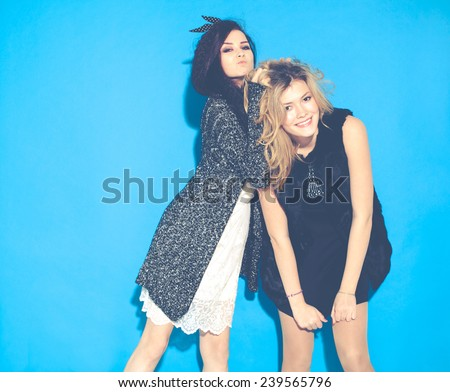 Fashionable beautiful young girlfriends standing together near a blue background. Two blondes and a brunette. Having funny and posing. Indoor. Toned in warm colors - stock photo