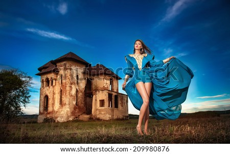 Fashionable beautiful young woman in long blue dress posing with old castle and cloudy dramatic sky in background. Attractive long hair brunette girl with elegant luxurious dress, outdoors shot. - stock photo