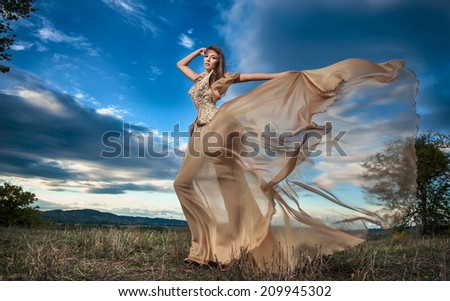 Fashionable beautiful young woman in nude colored long dress posing outdoor with cloudy dramatic sky in background. Attractive long hair brunette girl with elegant luxurious dress, outdoors shot. - stock photo