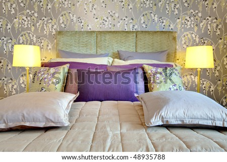 Fashionable bed with silk headboard dressed with brightly colored cushions and pillows, matching duvet, contemporary wallpaper and glass table lamps