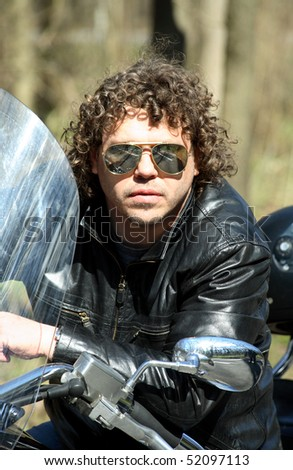 Fashionable biker with curly hair sitting on his motorcycle - stock photo
