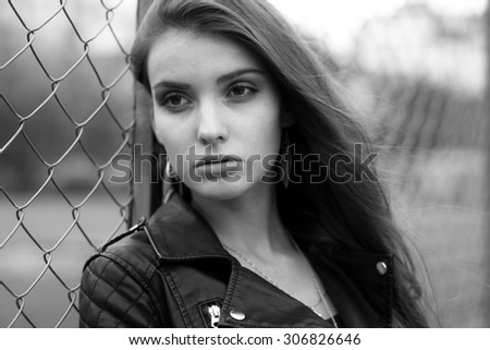 Fashionable black and white photo from a magazine. beautiful young rocker in a heavy leather jacket, with long beautiful black hair posing on the background grid and Park - stock photo