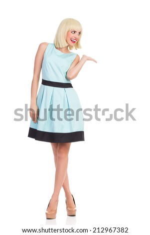 Fashionable blond female in light blue color dress posing with hand raised and presenting product. Full length studio shot isolated on white. - stock photo