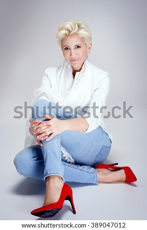 Fashionable blonde adult woman posing in studio, wearing jeans and red high heels. Short hairstyle. - stock photo