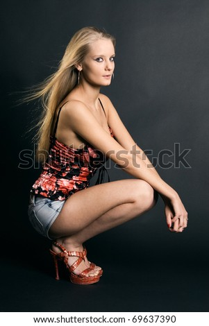 Fashionable blonde in denim shorts sitting on a dark background posing. - stock photo