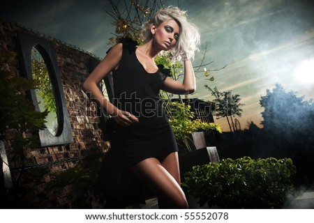 Fashionable blonde posing over evening sky - stock photo