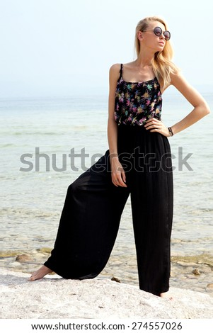 Fashionable blonde sexy woman posing on the beach. Sunny day. - stock photo