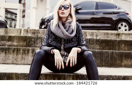 Fashionable blonde young woman in sunglasses sitting. Car on background.  - stock photo
