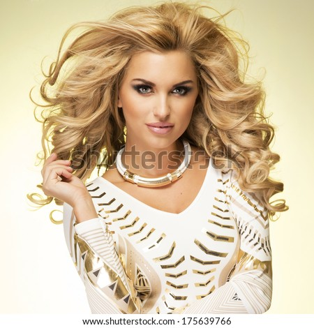 Fashionable blonde young woman posing, looking at camera. Studio shot. - stock photo