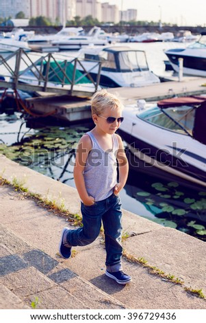fashionable boy wearing sunglasses and a hairstyle at the pier with yachts at sunset - stock photo