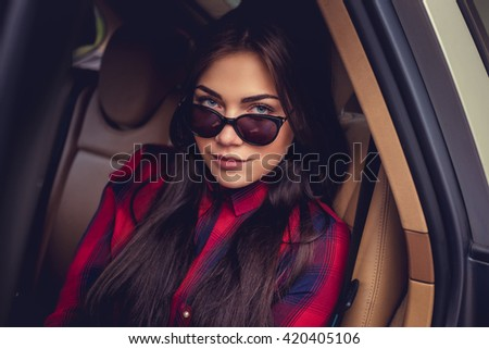 Fashionable brunette woman in sunglasses in a car's back seats. - stock photo
