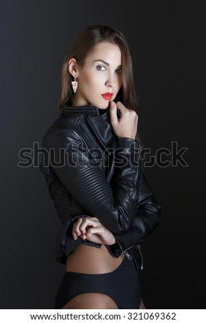 Fashionable brunette woman with red lips in leather jacket