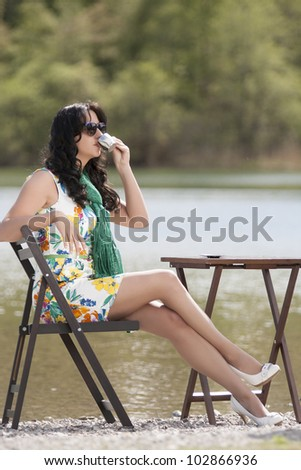 Fashionable business woman at a coffee break at the lake / coffee break - stock photo