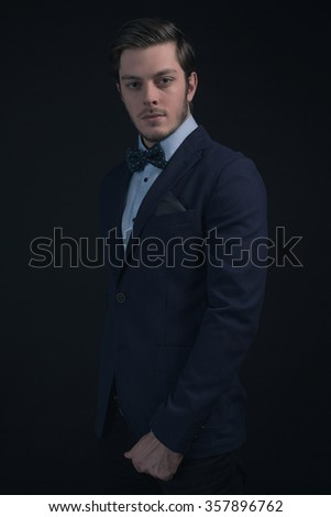 Fashionable businessman wearing blue jacket and shirt with bow tie.