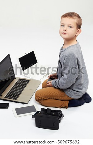 fashionable child with computers, tablets, phones, gadgets around. little boy and new technology. funny child. modern child. smart child. stylish child.internet child.gamer child