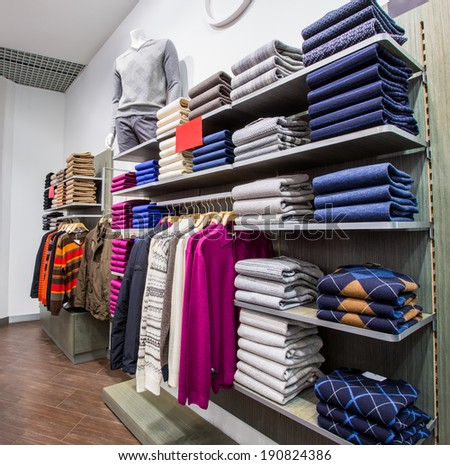 Fashionable clothing on hangers in shop - stock photo