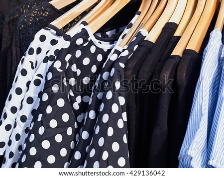 Fashionable design modern blouses on hanger rack display in a store       - stock photo