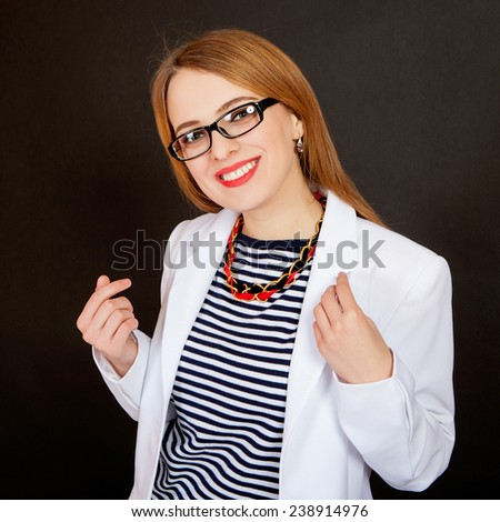 Fashionable doctor. Confident young female doctor in white uniform and glasses smiling while standing against black background - stock photo