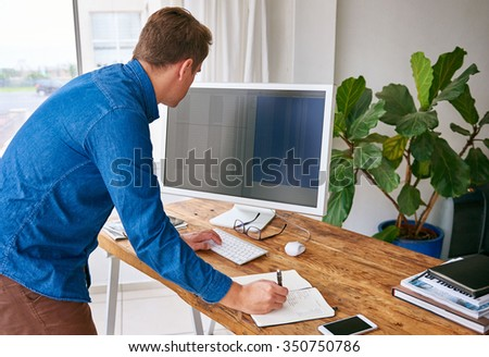 Fashionable entrepreneur standing at his desk in a contemporary office making notes in a journal while looking at something on his computer screen - stock photo