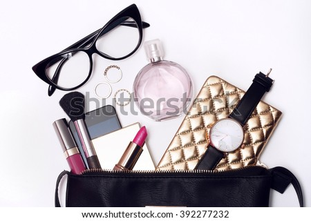 Fashionable female accessories watch glasses lipstick perfume and black purse. Overhead of essentials for modern young woman. - stock photo