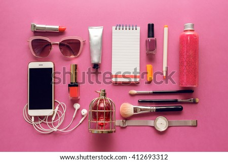 Fashionable female accessories watch, sunglasses, lipstick, mobile phone. Overhead of essentials for stylish young woman. Different objects on  pink  background . Bright summer colors.  - stock photo