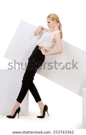 Fashionable female model posing at studio. Beauty, fashion photo. Clothing. Body care. Isolated over white. - stock photo