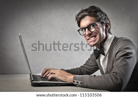 Fashionable forcibly smiling while using a laptop computer - stock photo
