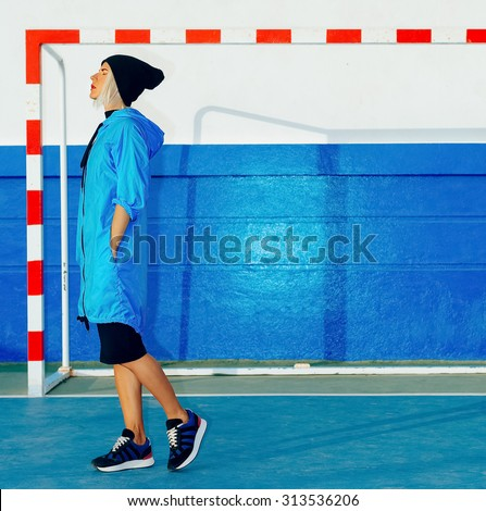 Fashionable Girl in bright blue coat in the stadium. Blue color in trend - stock photo