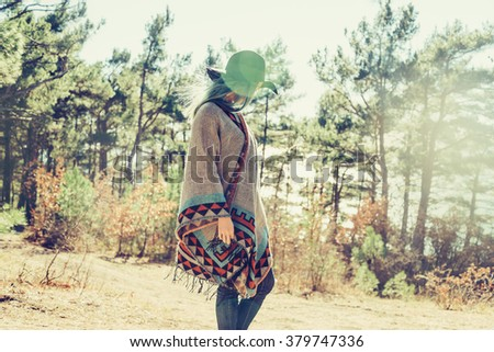 Fashionable girl in hat and poncho walking in forest among pine trees at sunny day - stock photo