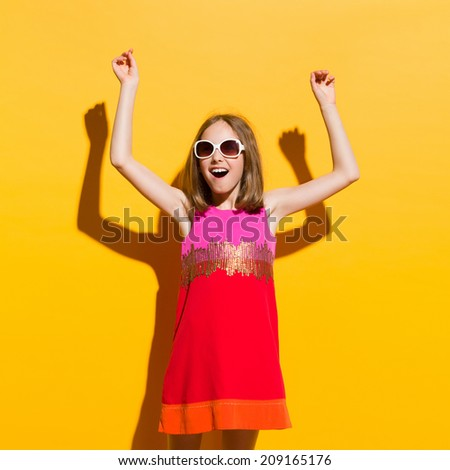 Fashionable girl in sunglasses and mini dress shouting with arms raised. Three quarter length studio shot on yellow background. - stock photo
