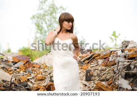 fashionable girl in white dress on the dirty industrial place - stock photo