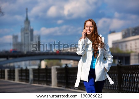 fashionable girl walking down the street and talking on the phone - stock photo