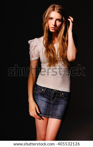 Fashionable girl wearing blue jeans shorts over black background