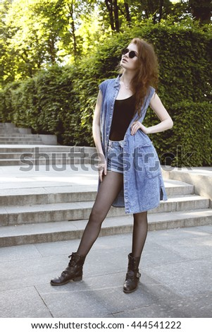 Fashionable glamorous girl with long curly hair wearing jeans shorts, denim weistcoat and round sunglasses posing at city streets. Fashion vogue style outdoor portrait - stock photo