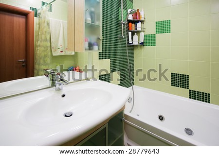 Fashionable green bathroom in a modern apartment - stock photo