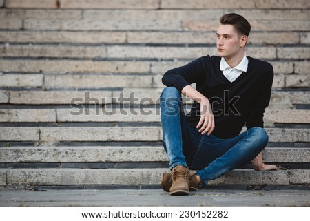 Fashionable handsome man model posing outdoors in summer day. Street fashion - stock photo