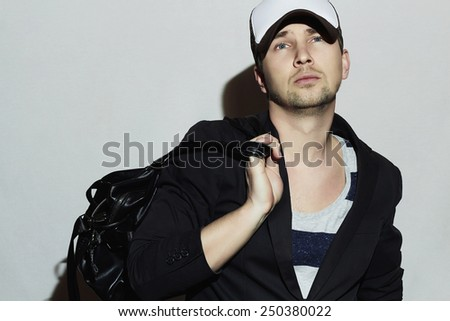 Fashionable Handsome Man with handbag. Stylish Boy in cap. Casual Fashion.Young man - stock photo