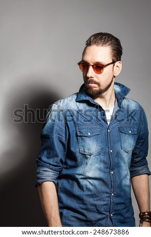 Fashionable handsome stylish bearded man in a denim shirt and sunglasses - stock photo