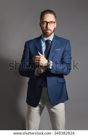 Fashionable handsome stylish bearded man with glasses and in blue blazer