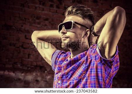Fashionable handsome young man posing outdoor. Brick wall background.