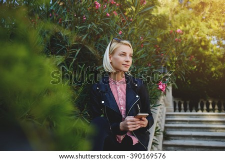 Fashionable hipster girl hold mobile phone and looking away while she standing in beautiful green park,gorgeous female typing text message on cell telephone while she resting in the fresh air outdoors - stock photo