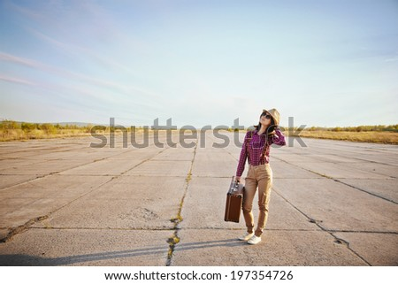 Fashionable hipster woman is standing on road with vintage suitcase