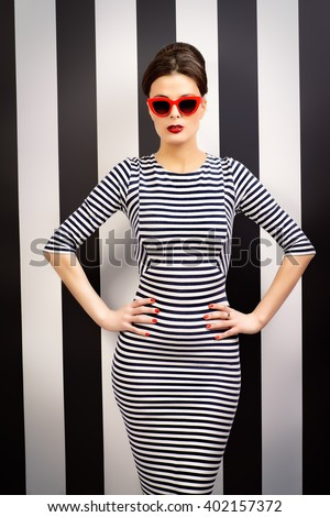 Fashionable lady in elegant dress and pin-up hairstyle posing at studio. Pin-up glasses, optics style. Beauty, fashion concept. - stock photo