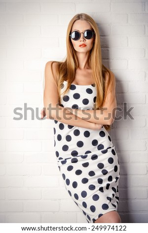 Fashionable lady in polka-dot dress posing near white brick wall. Beauty, fashion concept. Optics. - stock photo
