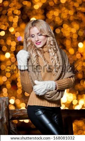 Fashionable lady  Wearing Cap And muffler Coat outdoor .Portrait of young beautiful woman in winter style.Bright picture of beautiful blonde woman with make up