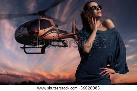 fashionable lady wearing sunglasses with helicopter in the background - stock photo